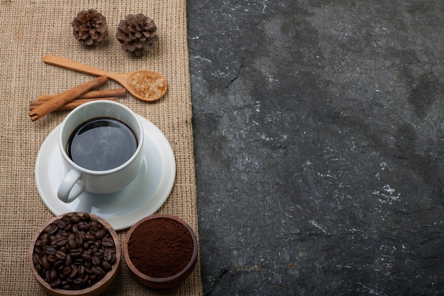 White cup coffee, coffee beans in wood cup , pine on burlap on black stone  textured