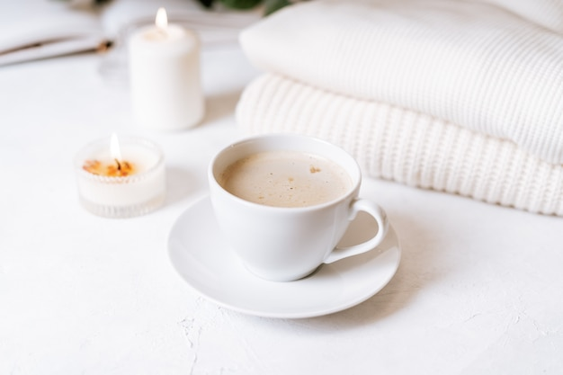 White cup of coffee, cotton, candles.