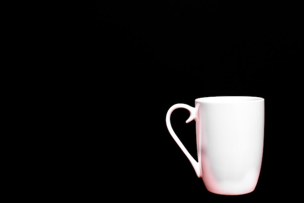 White cup of coffee, empty and blank, isolated on black with copy space.