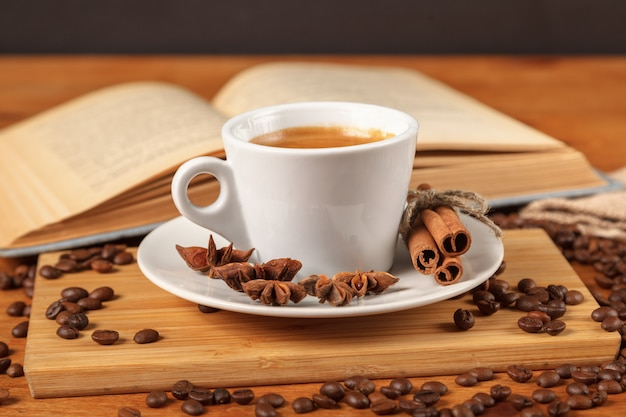 White cup of coffee espresso surrounded by of roasted coffee beans