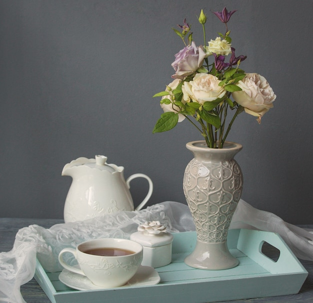 A white cup of coffee, kettle and vase of flowers