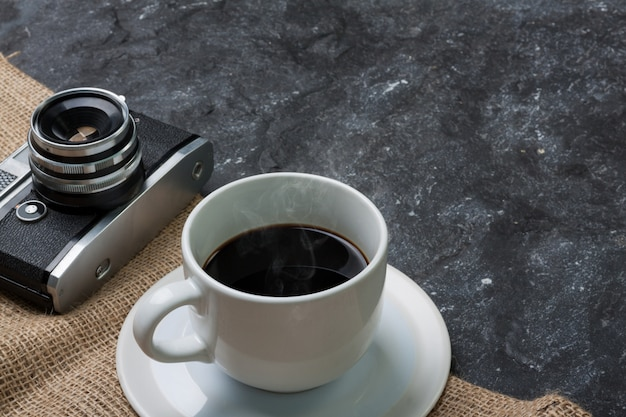 White cup coffee and old camera on burlap in black stone