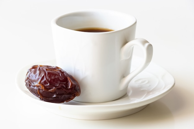 White cup of coffee and one dates white background isolated.