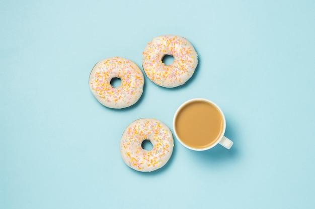 白いカップ、コーヒーまたは紅茶とミルクと青色の背景に新鮮なおいしいドーナツ。パン屋さんのコンセプト、焼きたてのペストリー、おいしい朝食、ファーストフード。