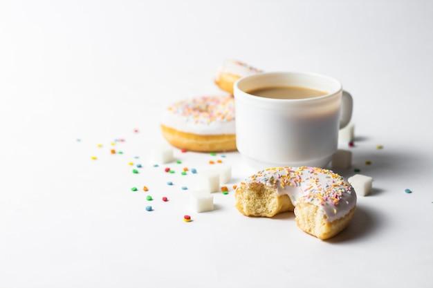 화이트 컵, 커피 또는 차 우유와 신선한 맛있는 도넛, 흰색 배경에 달콤한 여러 가지 빛깔 된 장식 사탕. 베이커리 개념, 신선한 파이, 맛있는 아침 식사, 패스트 푸드.