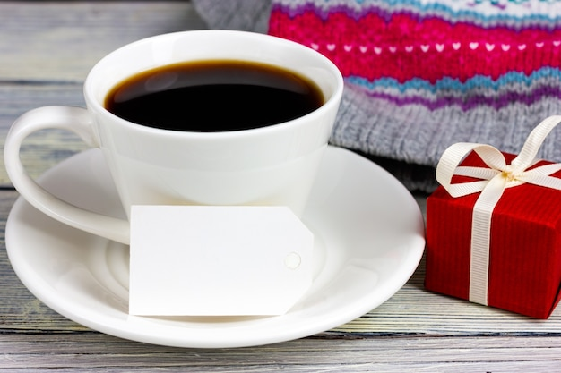A white cup of coffee, a paper note and a small red gift. place for your text. congratulations on valentine's day, anniversary.