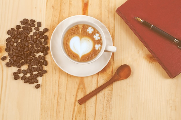 White cup of coffee on pine wood desktop table on top