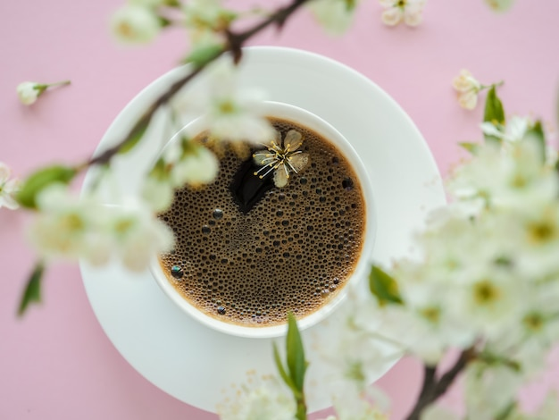 White cup of coffee and spring blossom flowers on pink table. morning romantic americano. cafe and bar, barista art concept. top view. flat lay