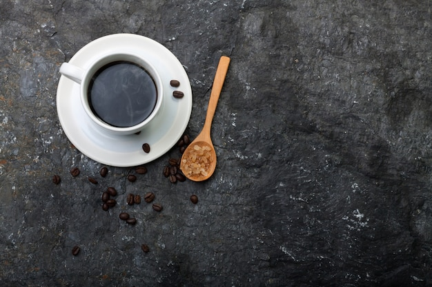 White cup coffee , sugar in wood spoon on black stone