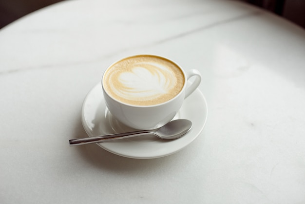 White cup of coffee on table