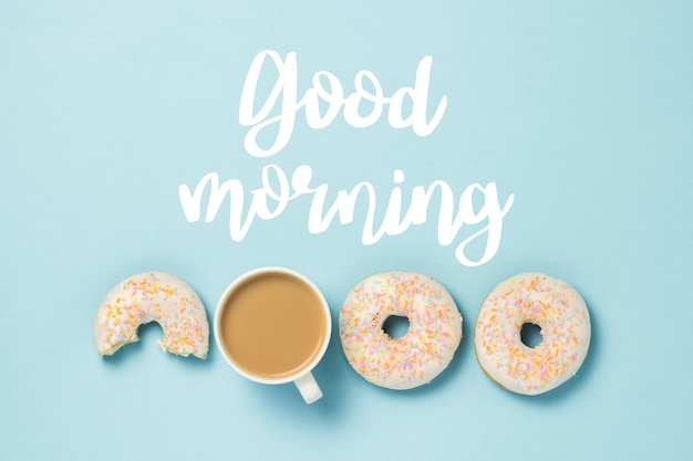 White cup, coffee or tea with milk and fresh tasty donuts on a blue. added text good morning. bakery concept, fresh pastries, delicious breakfast, fast food. flat lay, top view.