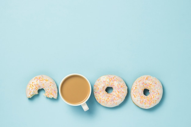 White cup, coffee or tea with milk and fresh tasty donuts on a blue background. bakery concept, fresh pastries, delicious breakfast, fast food. flat lay, top view.