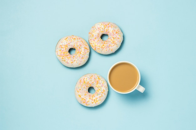 White cup, coffee or tea with milk and fresh tasty donuts on a blue background. bakery concept, fresh pastries, delicious breakfast, fast food.