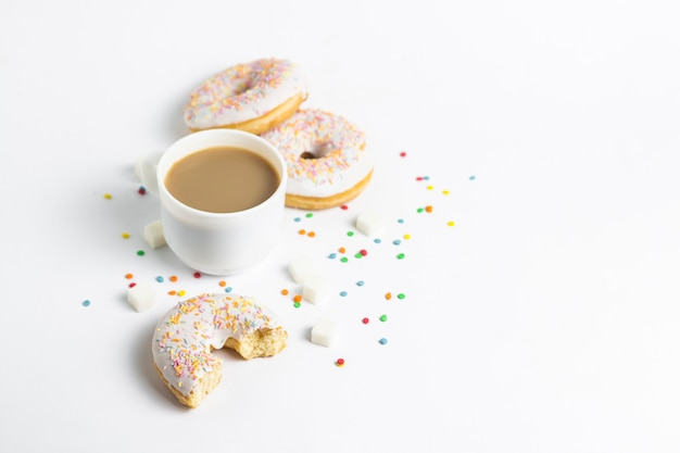 White cup, coffee or tea with milk and fresh tasty donuts, sweet multicolored decorative candy on a white background. bakery concept, fresh pastries, delicious breakfast, fast food.