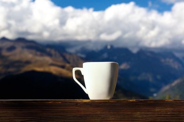 White cup of coffee and tea with steam on wood table over mountains landscape