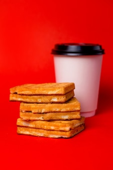 White cup of coffee and three waffles on red.