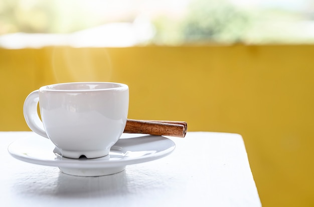 White cup of coffee on white table with yellow backgrund