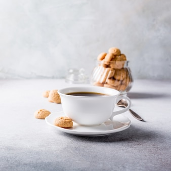 White cup of coffee with amaretti cookies