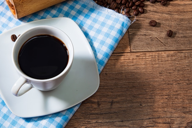 White cup of coffee with beans on wooden background.
