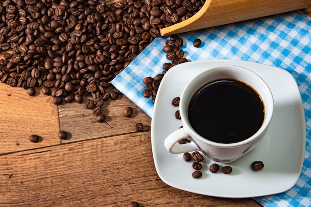White cup of coffee with beans on wooden background