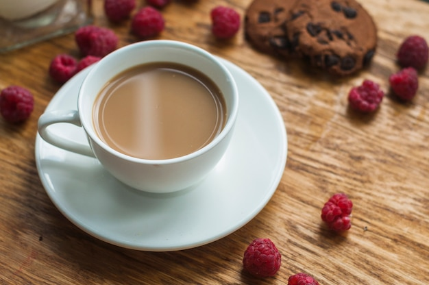 White cup of coffee with chocolate cookies and raspberries on wooden background