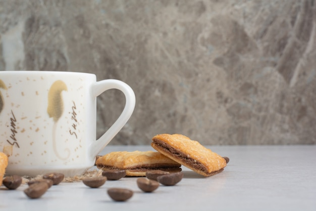White cup of coffee with crackers and coffee beans on white background. high quality photo