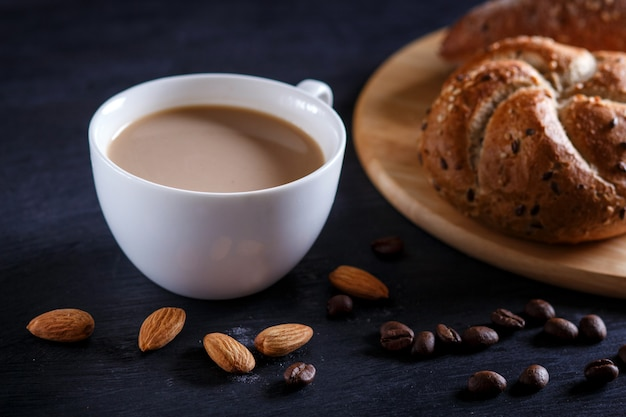 White cup of coffee with cream  and buns on a black background.