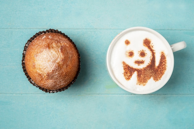 White cup of coffee with panda pattern on the foam and a cupcake,