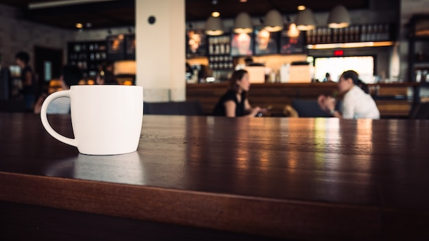 White cup of coffee on wooden surface