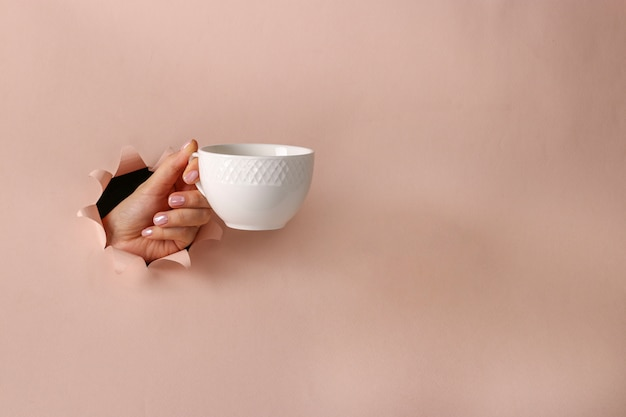White cup in a female hand through round hole in pink paper background, coffee time, copy space