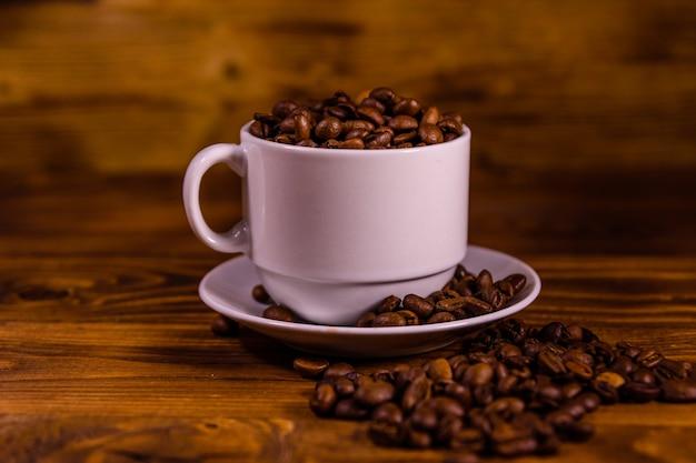 素朴な木製のテーブルの上にコーヒー豆で満たされた白いカップ