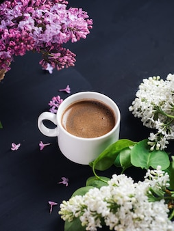 A white cup of fragrant coffee on a dark stone table with branches of purple and white lilacs. spring morning and mood
