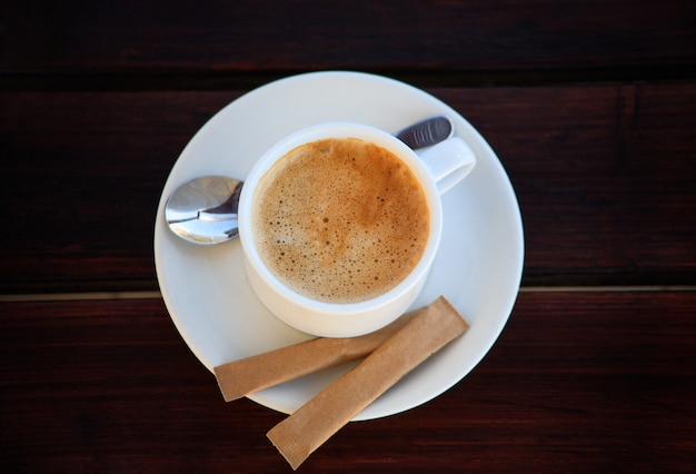 White cup of freshly brewed coffee with sugar