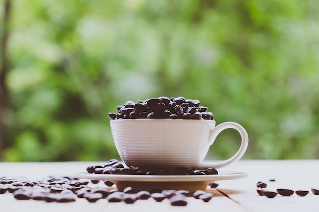 White cup full of coffee beans on roasted coffee beans and wooden table in nature background