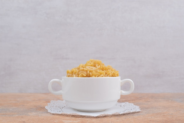A white cup full of unprepared fresh macaroni on marble background. high quality photo