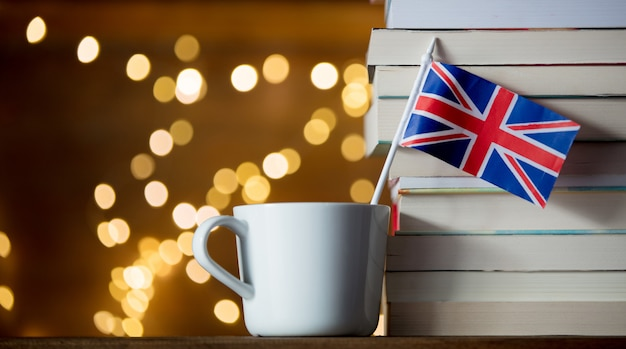 White cup and great britain flag near pile of books