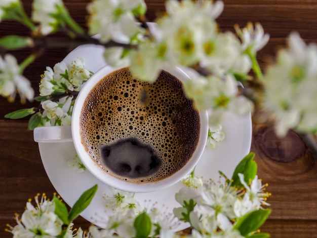 A white cup of hot aromatic coffee and branch of a blossoming cherry tree on a wooden. flat layout. view from above. spring morning americano. cozy, mood, lifestyle, still life concept.