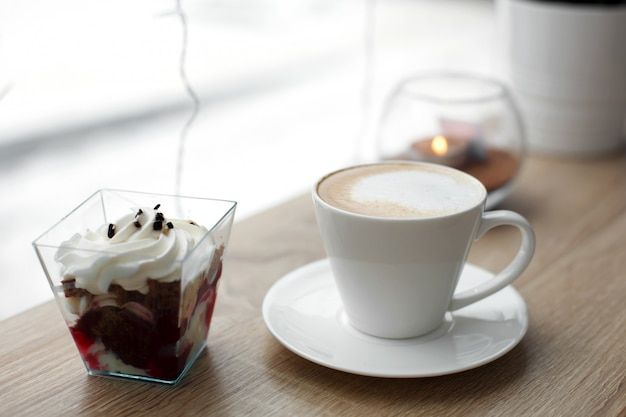 White cup of hot cappuccino on white saucer and red velvet dessert on wooden bar table next to window