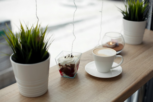 White cup of hot cappuccino on white saucer and red velvet dessert on wooden bar table next to window.