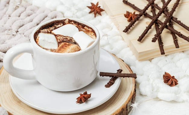 White cup of hot chocolate with marshmallows, chocolate sticks.
