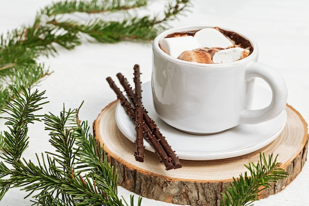 White cup of hot chocolate with marshmallows decorated fir twigs