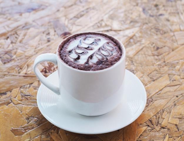 White cup of hot chocolate on wooden table.