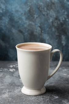 A white cup of hot cocoa on table