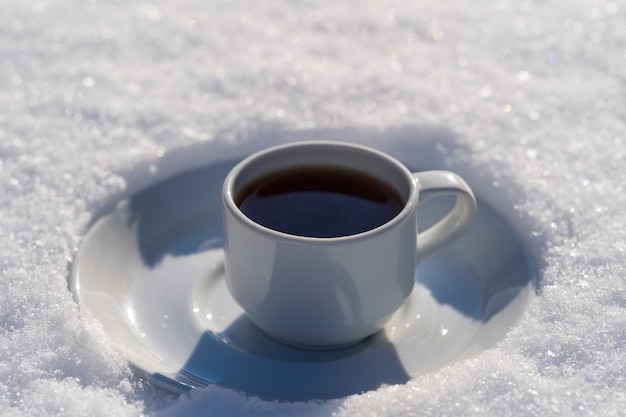 White cup of hot coffee on a bed of snow and white background, close up. concept of christmas winter morning
