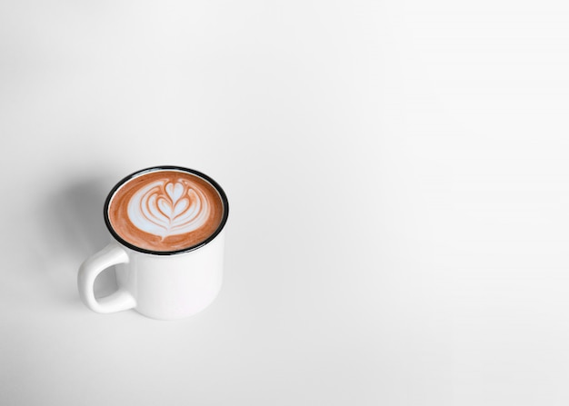 A white cup of hot coffee latte art on white background with copy space. top view
