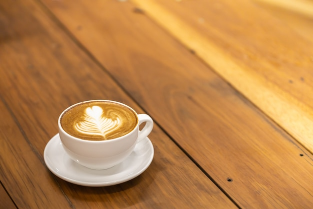 White cup of hot coffee latte with heart shape and flower art on wooden table.