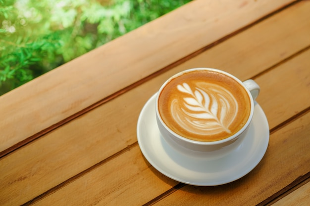 White cup of hot coffee latte with milk foam heart shape art with green nature.