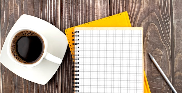 White cup of hot coffee and notebook on wood table