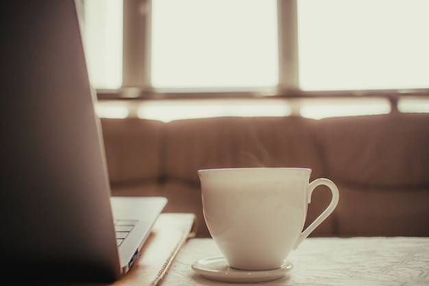 White cup of hot coffee on the table of a freelance man.