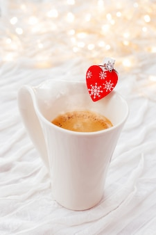 White cup of hot coffee with decorative heart and engagement diamond ring, symbol of love and marriage.
